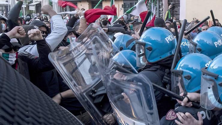 Demonstranten stoßen bei einem Protest gegen die Corona-Maßnahmen, die von Premierminister Conte erlassen wurden, mit Polizisten aneinander. Foto: Roberto Monaldo/LaPresse/AP/dpa