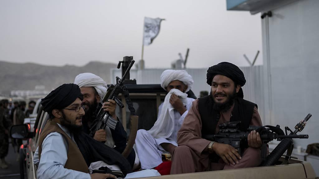 Taliban-Kämpfer sitzen auf der Ladefläche eines Autos auf dem Gelände des Flughafens in Kabul und halten Waffen in ihren Händen. Foto: Bernat Armangue/AP/dpa