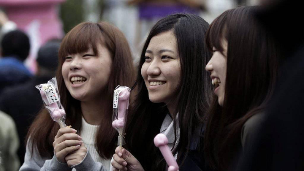 Frauen posieren beim alljährlichen Kanamara Matsuri mit phallusförmigen Süssigkeiten.