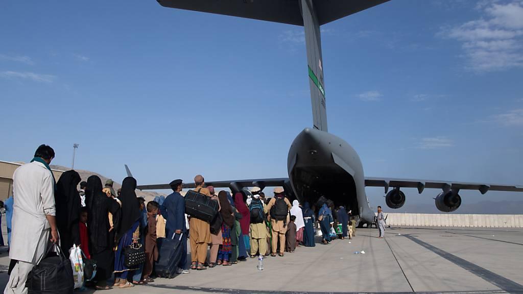 HANDOUT - Afghanische Flüchtlinge besteigen ein US-Militärflugzeug von Typ Boeing C-17 Globemaster III am Hamid Karzai International Airport. Foto: Msgt. Donald R. Allen/U.S. Air/Planet Pix via ZUMA Press Wire/dpa - ACHTUNG: Nur zur redaktionellen Verwendung und nur mit vollständiger Nennung des vorstehenden Credits