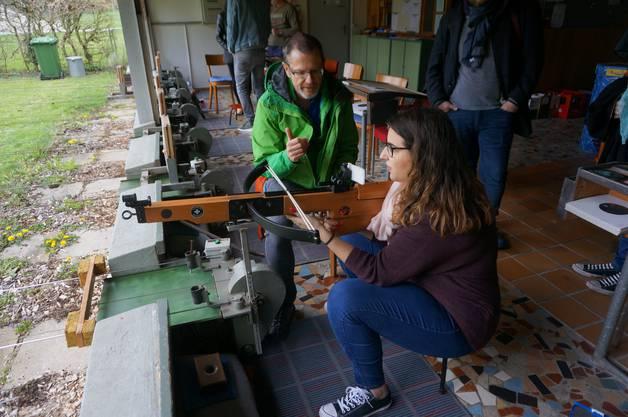 Der 55-jährige Hanspeter Blaser instruiert Besucherin Alessandra Marangi, wie mit der Armbrust umzugehen ist.