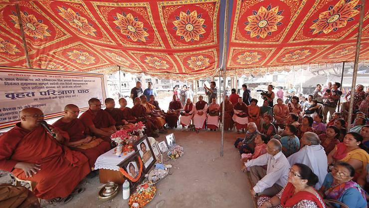 Buddhistische Mönche beten mit Angehörigen für die Opfer des Erdbebens in Nepal vor einem Jahr.