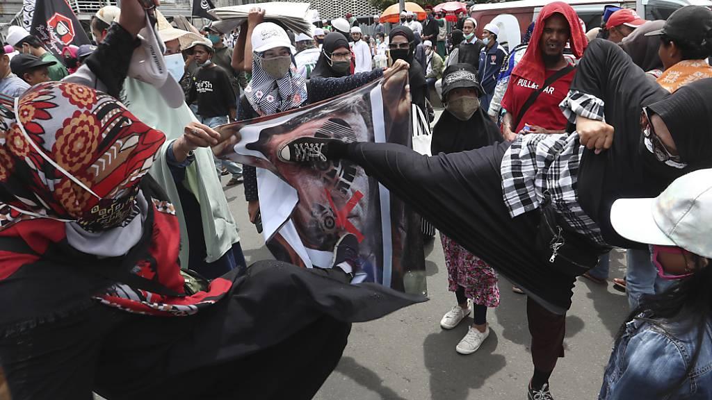Indonesische Muslime protestierten gegen Macron und seine entschiedene Unterstützung säkularer Gesetze, die Karikaturen des Propheten Mohammed zur Meinungsfreiheit zählen. Foto: Achmad Ibrahim/AP/dpa