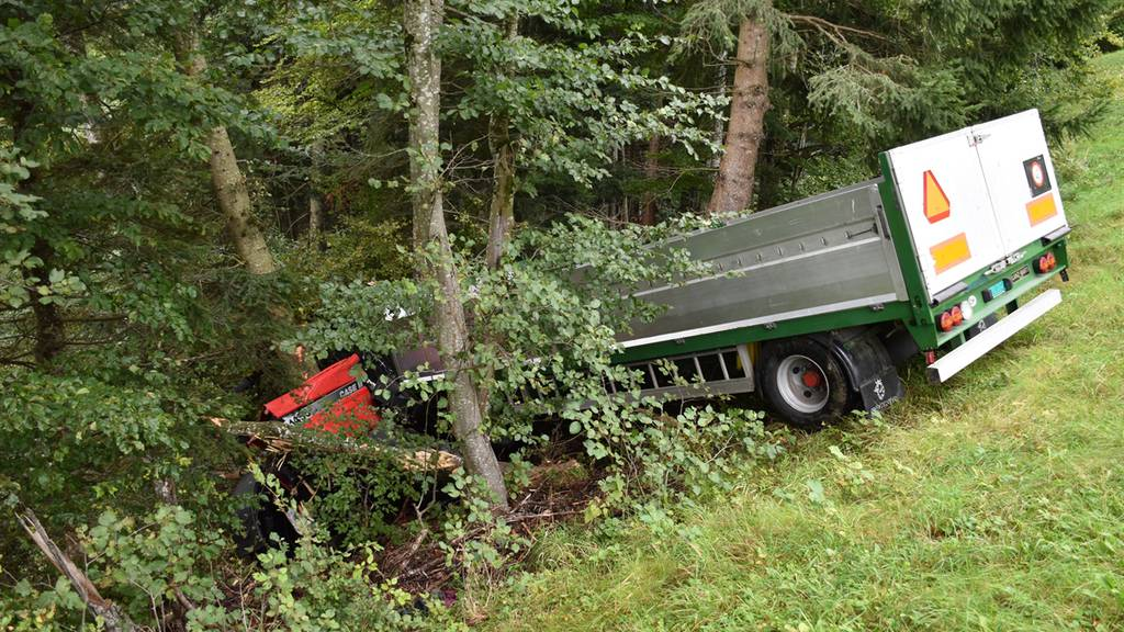 Traktor und Anhänger rollen Abhang hinunter