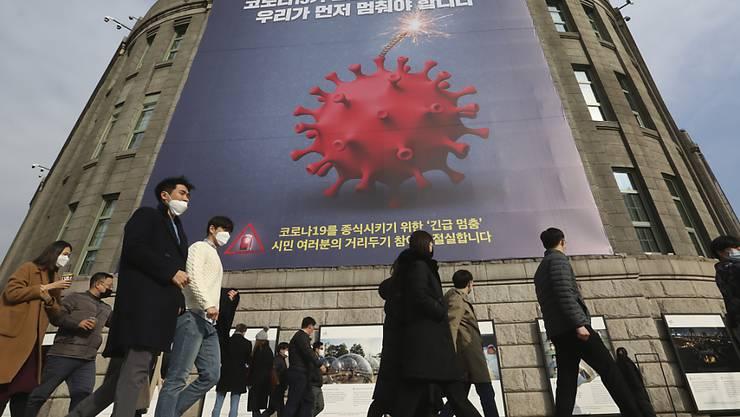 Menschen, die Gesichtsmasken tragen, gehen vor dem Rathaus von Seoul unter einem Transparent, das auf eine verstärkte soziale Distanzierungskampagne hinweist vorbei. Foto: Ahn Young-Joon/AP/dpa