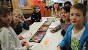 Eine aufgeweckte Schülerschar gestaltet Seiten für ein Bilderbuch.