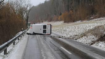 Der Lieferwagen kam wegen Glatteis ins Schleudern, fuhr die Böschung hoch, kippte dadurch auf die linke Seite und blieb so mitten auf der Strasse liegen.