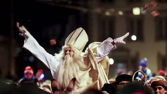 St. Nikolaus reitet auf dem Esel in Freiburg durch die Strassen und verteilt Lebkuchen. In der Verkleidung des Samichlaus steckt traditionsgemäss ein Schüler, der im Anschluss an den Umzug in einer Rede einen ironische Bilanz zum Jahr zieht.