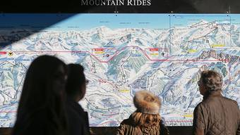 Touristen konsultieren eine Übersichtskarte der Gstaader Bergbahnen. Nach finanziellen Schwierigkeiten sind die Bahnen in den letzten Monaten saniert worden. Eine wichtige Rolle spielten dabei finanzkräftige private Investoren.