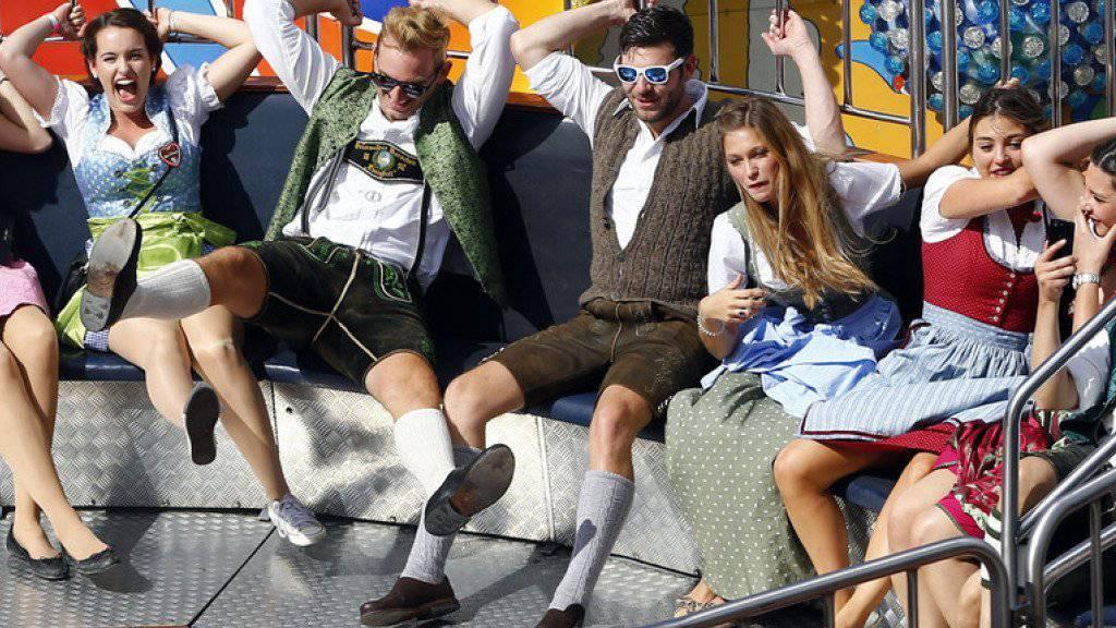 Junge Menschen in Trachten vergnügen sich am Oktoberfest.