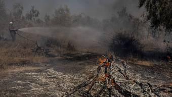 Ein Feuerwehrmann arbeitet bei der Löschung eines Brandes an der israelischen Grenze zum Gazastreifen, der durch einen Brandballon von Palästinensern verursacht wurde. Foto: Tsafrir Abayov/AP/dpa