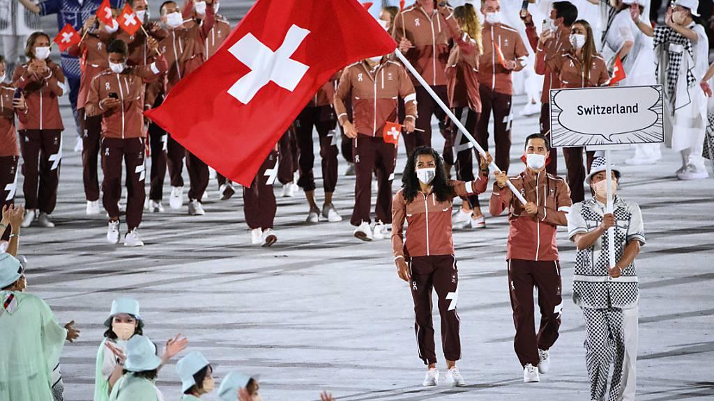 Max Heinzer und Mujinga Kambundji tragen die Schweizer Fahne ins Olympiastadion in Tokio