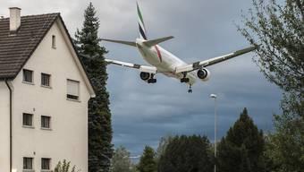 Ein Flugzeug fliegt im August 2014 ueber ein Wohngebiet in Kloten.