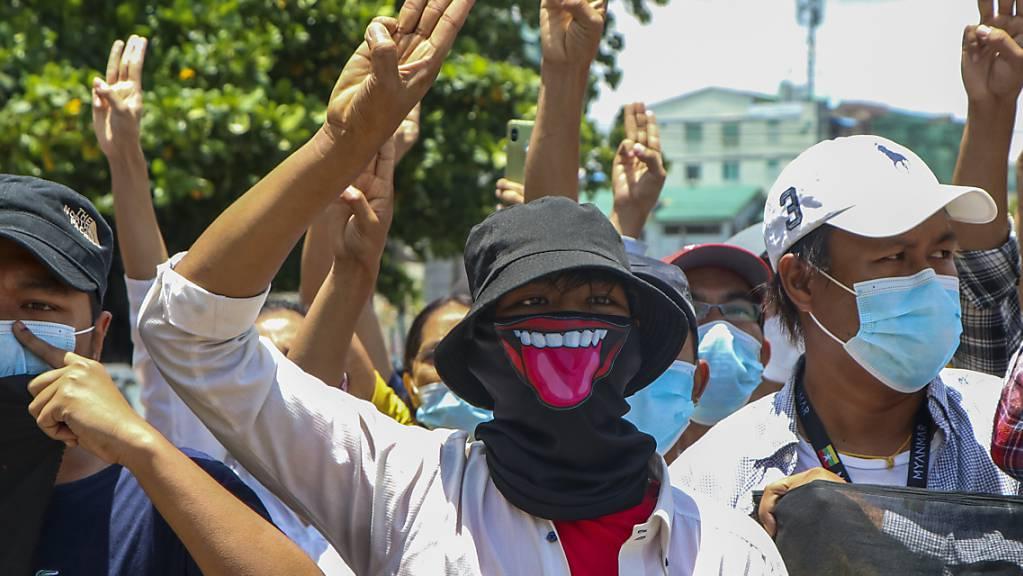 Demonstranten zeigen den Drei-Finger-Gruss, zum Zeichen des Widerstands, bei einer Protestaktion gegen den Militärputsch in Myanmar.