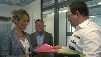 Felix Grendelmeier, Organisator des Protest-Grillens gegen die Asylunterkunft in Aarburg, übergibt Regierungsrätin Susanne Hochuli und ihrem Sprecher Balz Bruder die Petition: «Nein! zum geplanten Mega-Asylzentrum an der Lindengutstrasse in Aarburg».