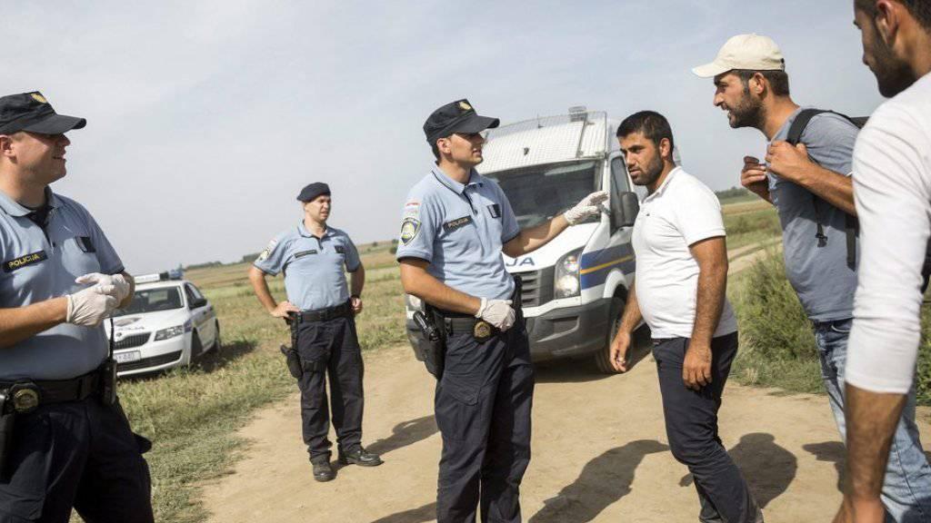 Kroatische Polizisten greifen Flüchtlinge an der Grenze zu Serbien auf.