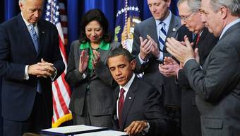 Kongressabgeordnete klatschen, nachdem Präsident Obama das Kompromisspaket unterzeichnet hat