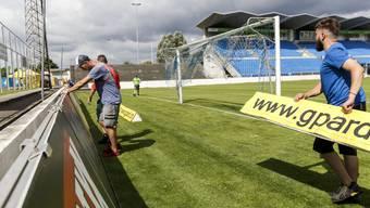 Uhrencup: Mitarbeiter der Stiftung Schmelzi befestigen Banden im Stadion Brühl