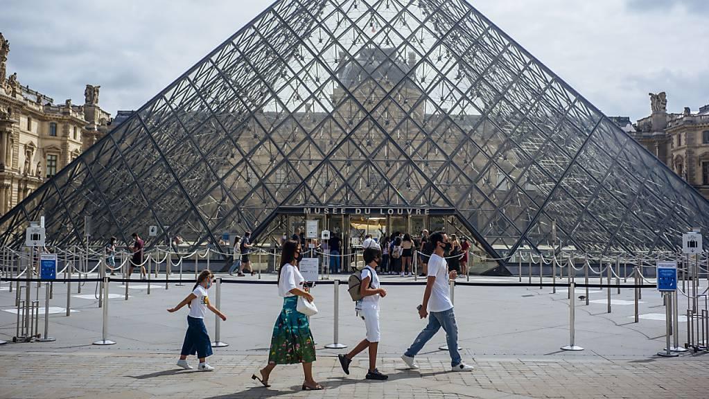 ARCHIV - Eine Familie mit Schutzmasken geht am Louvre vorbei. Foto: Kamil Zihnioglu/AP/dpa