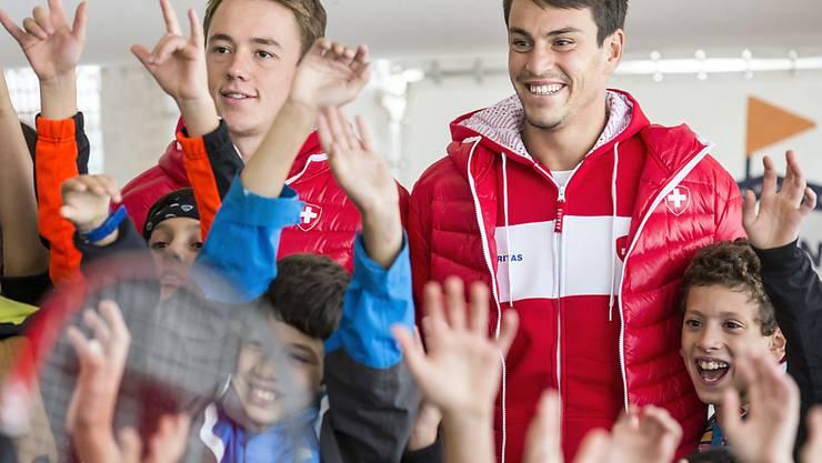 Das Schweizer Doppel Adrian Bodmer (links) und Luca Margaroli, umringt von jungen Fans