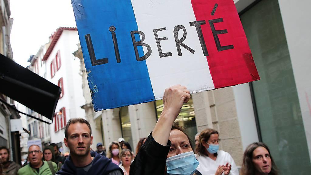 Eine Protestteilnehmerin hält während einer Demonstration ein Transparent in den Farben der Trikolore, mit der Aufschrift «Freiheit». Foto: Bob Edme/AP/dpa