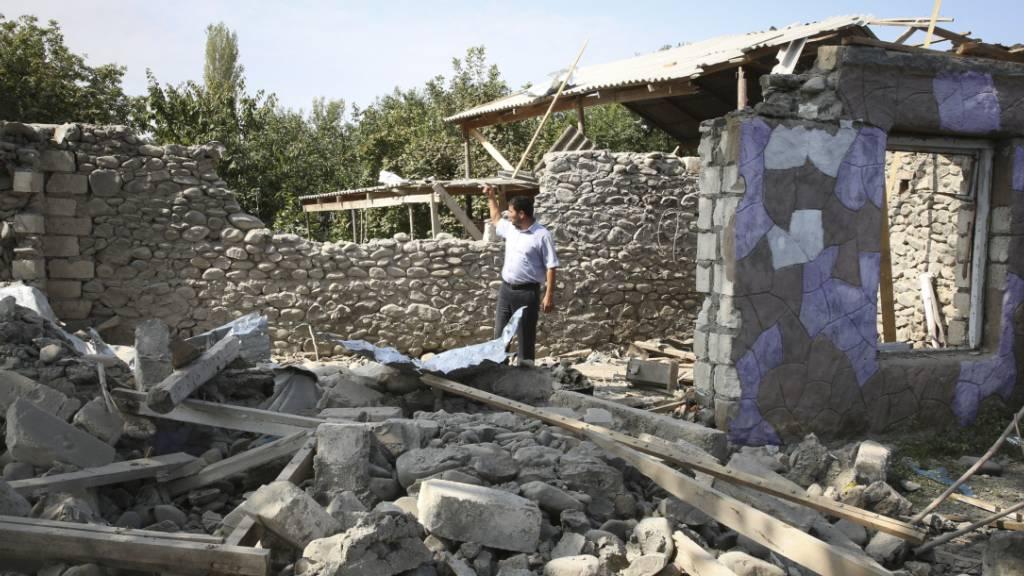 Ein Mann steht in den Ruinen eines Hauses, das angeblich während der Kämpfe beschädigt wurde. Foto: Aziz Karimov/AP/dpa