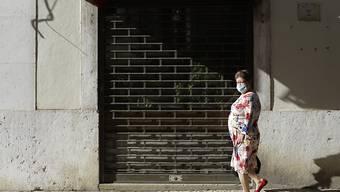 Eine Frau mit einer Gesichtsmaske geht an einem geschlossenen Restaurant in der Innenstadt vorbei. Foto: Armando Franca/AP/dpa
