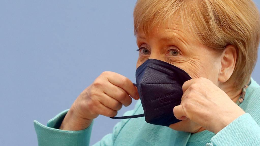 Bundeskanzlerin Angela Merkel (CDU) setzt sich ihre Maske auf.