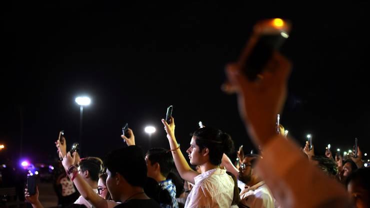 Mexikanische Bürger halten an der US-amerikanischen Grenze zum Gedenken an die Opfer von El Paso ihre leuchtenden Handys in die Luft.