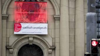 Der Stadtluft-Anzeiger an der Heiliggeist-Kirche in Bern leuchtete grösstenteils rot - ein Zeichen für eine zu hohe Stickoxid-Belastung der Luft. (Archivbild)