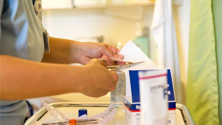 Ungedeckte Kosten für Verbrauchsmaterial. Eine Pflegerin bereitet einen Wundverband vor.