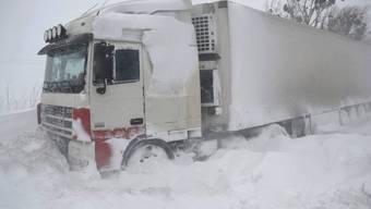 Ein Lastwagen steckt im Schnee fest (Symbolbild)