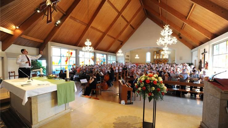 Igor Retnev, Leiter des Kirchenchors Wolfwil, dirigiert in der Kirche die 250 Sängerinnen und Sänger aus dem Thal und Gäu.