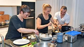 Andrea Burlet (links) und Christine Dubach (Mitte) beim Zubereiten der Vorspeise; rechts Stefan Burlet.