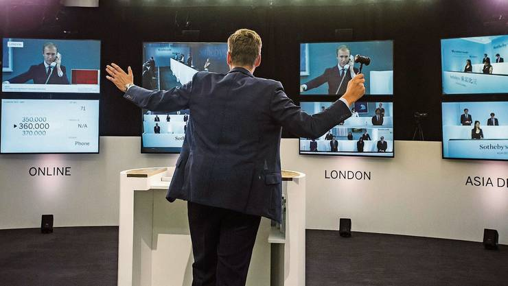 Ein Auktionator tanzt vor Bildschirmen und dirigiert Kollegen und Kolleginnen mit Bietern aus 47 Ländern am Telefon.