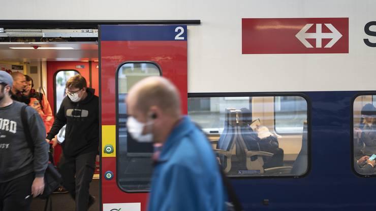 Zwei, die als Exoten gelten: Pendler mit Schutzmasken entsteigen einem Regionalzug.