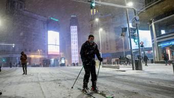 Ein Mann nutzt den Schnee als Skipiste.