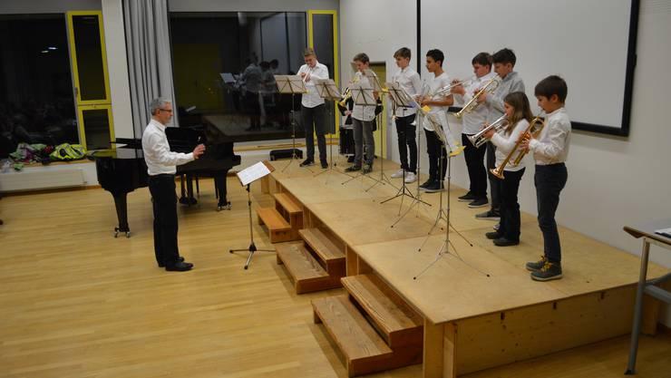 Acht Musikschülerinnen und Schüler spielen am klassischen Konzert Trompete.