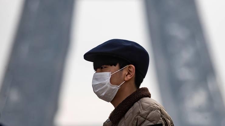 Chinesischer Tourist am Eiffelturm: In Paris greift die Angst vor dem Virus um sich.