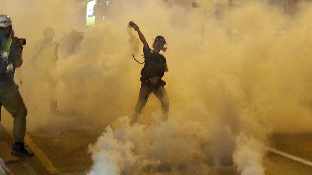 Ein Demonstrant in Hongkong wirft einen Tränengaskanister zurück.