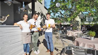 Rahel, Jonas und Simon Stäuble (v.l.) servieren in ihrem Biergarten unter anderem Lägere Bräu und kalte Plättli.