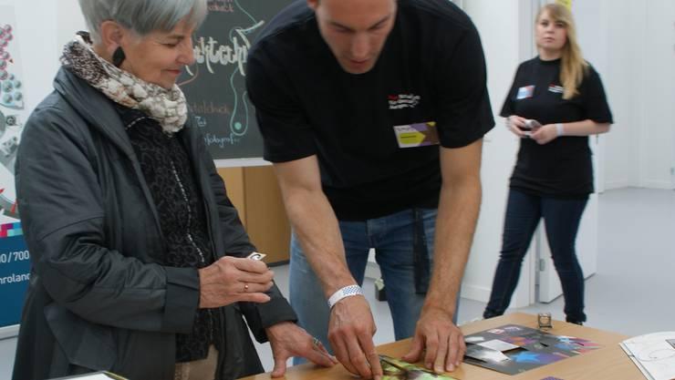 Ein Drucktechnologe erklärt einer Besucherin den Reliefdruck. SIH