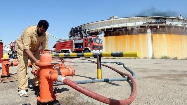 Ein Mann steht bei einem brennenden Öltank in der Hafenstadt Brega (Symbolbild)