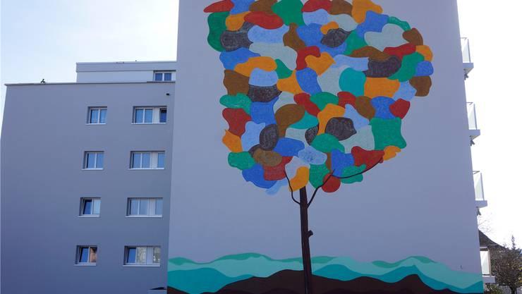 Das Bild eines farbigen Baumes schmückt die Fassade.