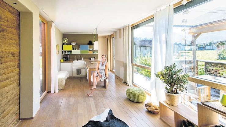 Viel Holz und Glas prägen das Innere in Tanja Schindlers Minihaus. Die Wände sind aus Lehm, die Möbel lassen sich je nach Bedarf für unterschiedliche Zwecke einsetzen.
