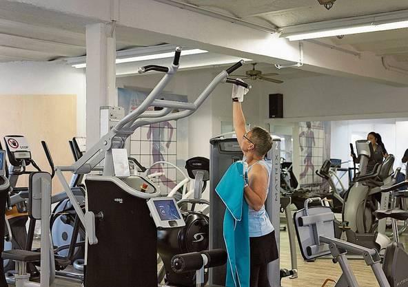 Anita Räss desinfiziert eines der Trainingsgeräte, ehe sie sich dransetzt. Während des Shutdowns hat sie alleine im Estrich trainiert. Bild: Britta Gut