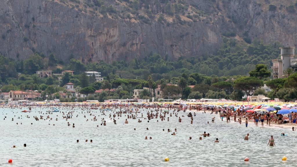 Zahlreiche Menschen besuchen der Strand von Mondello in der Nähe der Stadt Palermo. Die Hitzewelle in Süditalien mit Temperaturen von bis zu 45 Grad Celsius hält weiter an. Foto: Alberto Lo Bianco/LaPresse via ZUMA Press/dpa