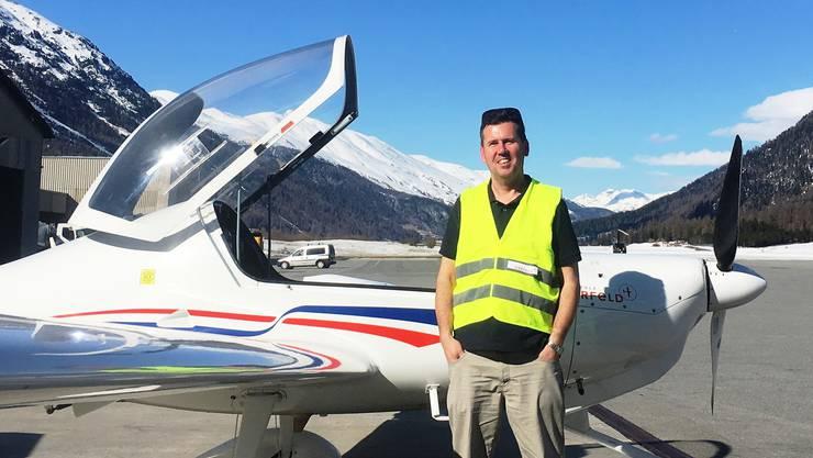 Pfarrer Wieslaw Reglinski steht vor einem Sportflugzeug auf dem Flughafen Samedan.