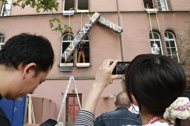 Der japanische Performancekuenstler und Architekt Noriyuki Kiguchi (mit rotem Megaphon) treibt mit seiner Crew und Passanten ein riesiges Schlangengebilde durch den Kopfbau der Kaserne vom Kasernenareal zum Rhein (4)