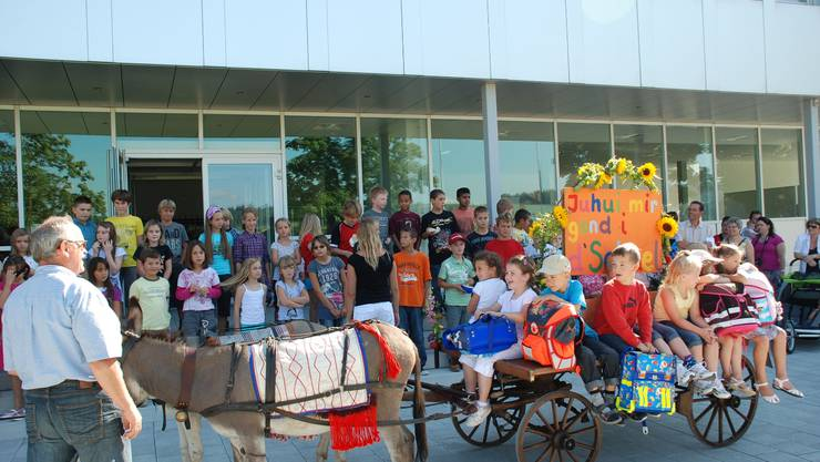Die Kinder kommen per Eseltexi in der Schule an.